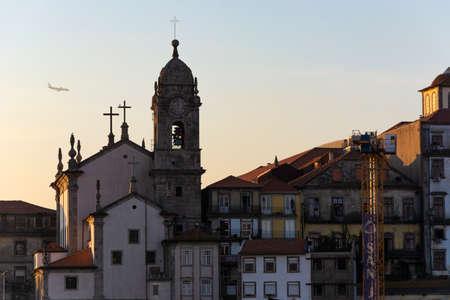 Porto, Portugal - 01/07/2020: Porto, Portugal. View to the Paroquial de Nossa Senhora da Vitória church. Plane preparing for landing in the background. Sunset.