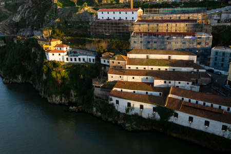 Porto, Portugal - 02/15/2020: Port wine cellars in douro river bank. White buildings with orange roof lit by the warm sunset light.