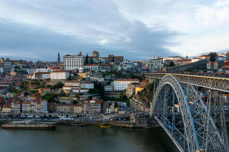 Porto, Portugal - 02/15/2020: Porto view, with Dom Luís Bridge and metro. Sunset, cloudy sky. Boats on the river.
