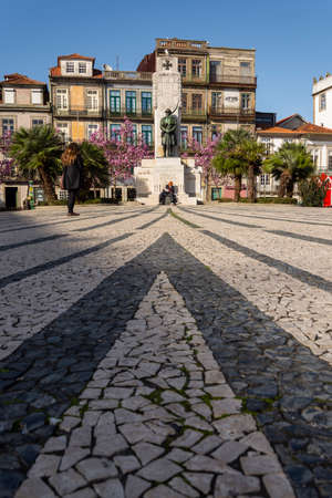 Porto, Portugal - 02/17/2020: Carlos Alberto Square. Memorial to the soldiers of the first first world war. Traditional portuguese houses in the background. Trees with pink flowers.