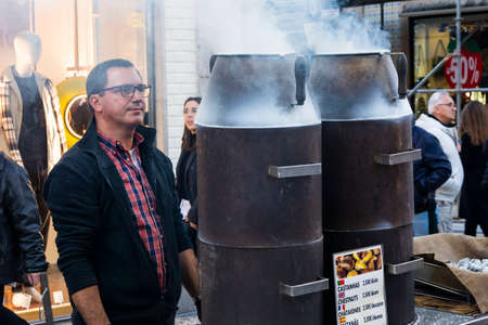 Porto, Portugal - 11/23/2019: Porto, Portugal. Man cooking chestnuts. Smoke coming out of the chestnut oven.