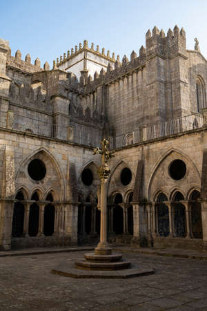 Porto cathedral seen from the inner courtyard. Old cross made of stone in the middle. Building made of stone Blue sky. Porto, Portugal.