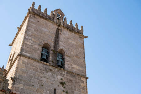 Church tower with bells. Exterior of Nossa Senhora da Oliveira Church. Old medieval building. Blue sky. Guimarães, Portugal.