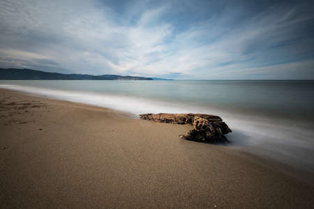 sidelight: Sandy beach and stone in the sea