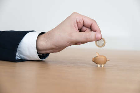 Viel zu kleine Schweinchen mit einer Hand Euro Fütterung Standard-Bild
