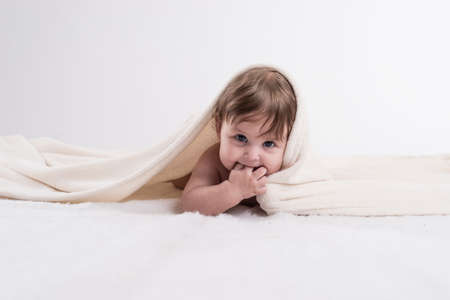 Happy baby under blanket advertising photography.