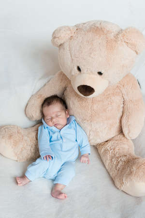 Newborn baby sleeping on stuffed animal. Stock Photo