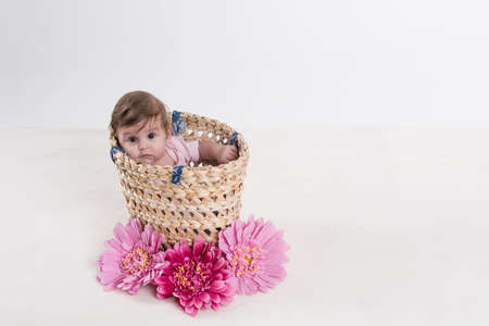 chill baby in basket with pink flowers.