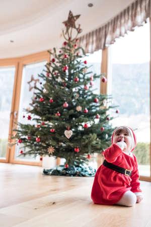 baby girl sitting under christmas tree. Stock Photo