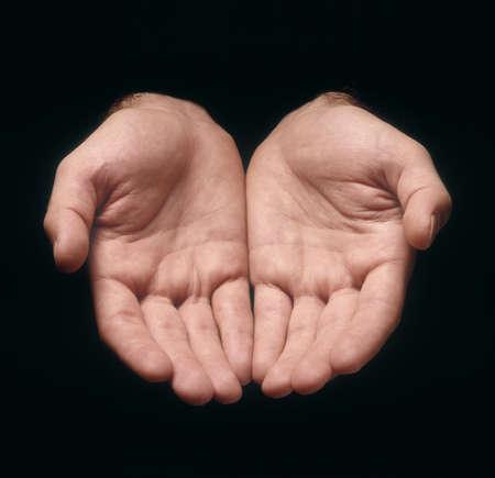 Due mani dell'uomo nell'offrire gesto contro sfondo nero
