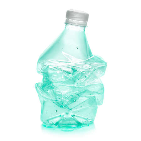 Squashed plastic bottle  in order to recycle in green color  Clipping path included photo