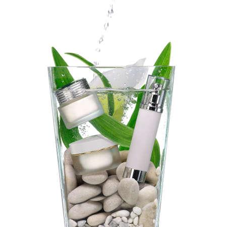 cosmetics: Cosm�ticos en un jarr�n de agua con piedras y hojas verdes