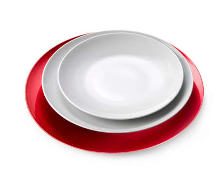 white color: White plates over a red tray isolated on white background.Clipping path Stock Photo