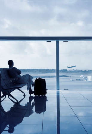 Lady silhouette in a lobby airport waiting for her flight, looking through a glass with solar protection.