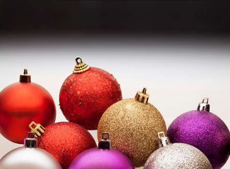bakground: Colorful christmas balls against a gray gradient background.