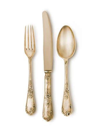 La coltelleria dorata ha impostato contro priorità bassa bianca con un'ombra molle. Pezzi davvero d'argento con segni e texture antiche. Tracciato di ritaglio Archivio Fotografico