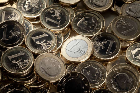 One euro coin prominent from among many euro pieces. Imagens