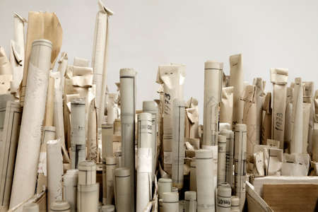A large amount of old stacked architectural rolls and plans Standard-Bild