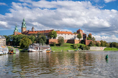 Barges in front of Wawel Castle on waterfront of Vistula river in Cracow, Poland