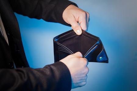 Broke businessman opening empty wallet showing he has no money