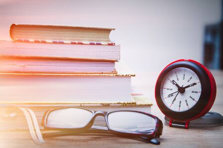Alarm clock, glasses and books on the table