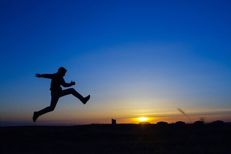 Silhouette of a man running on meadow