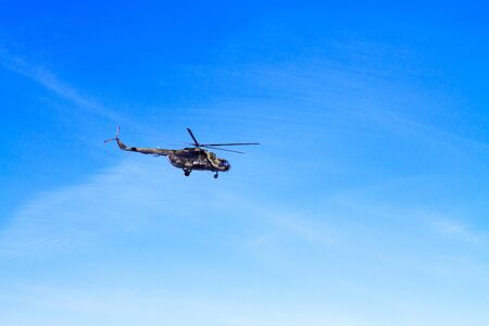 A camouflaged military helicopter in flight against a blue sky