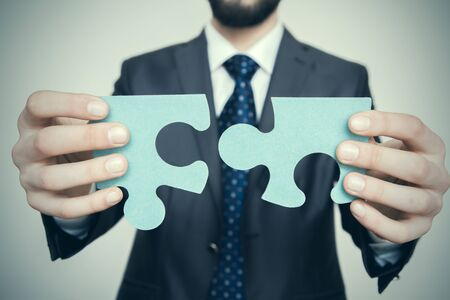 Businessman holding two blank white puzzle pieces in his hands