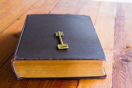 Old book with key on it on a wooden table.