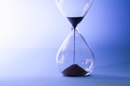 Sand running through an hourglass measuring passing time.