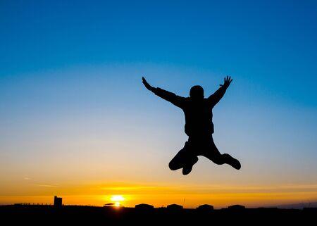 Silouhette of a man jumping at sunset Standard-Bild