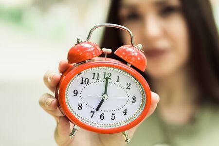 Beutiful girl holding orange alarm clock.