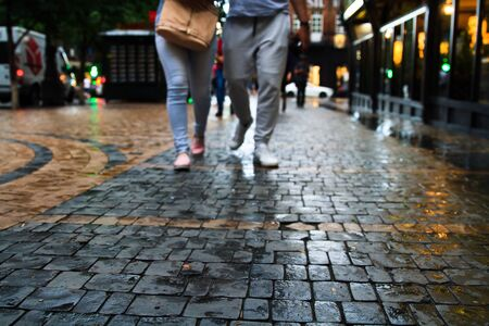 Pedestrians walking on the wet sidewalk at night.  Stock fotó