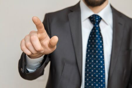 Hand of a businessman with raised index finger pointing out.
