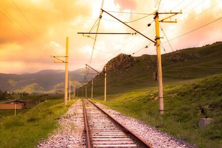 Railway track and power lines at sunset.