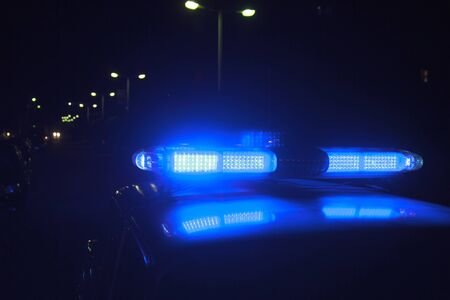Police at night in the car with blue siren flasher. Foto de archivo