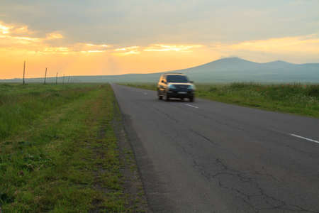 Black modern car on a road with sunset background. 写真素材