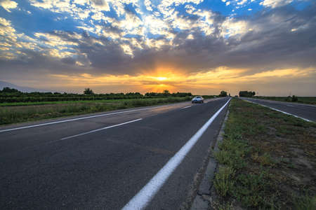 Dramatic sunset landscape with a countryside road and a car.