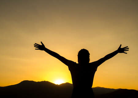 Silhouette of a woman raising her hands at sunset.  스톡 콘텐츠