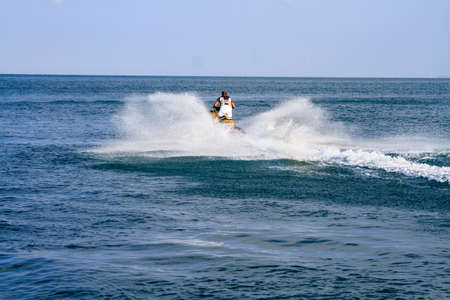 Young man skiing on water scooter.