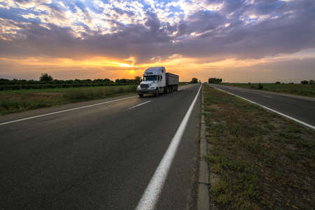 Big truck on a countryside road with dramatic sunset background.