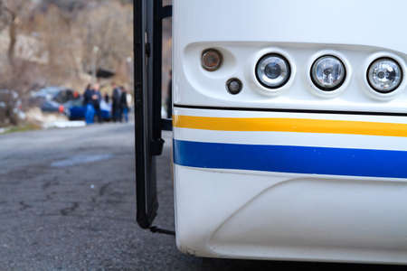 White bus on parking frontally close up with group of tourists background.