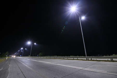 Empty countryside road at night with street lights.
