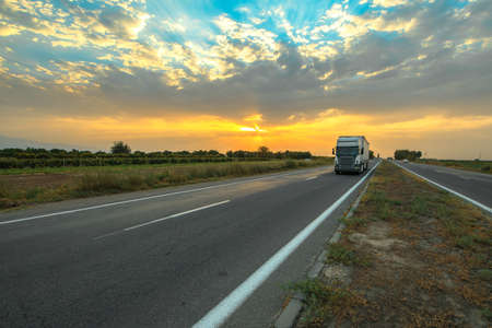 Big truck on countryside highway at beautiful cloudy sky sunset.