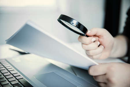 Woman holding magnifying glass over notebook, search concept.