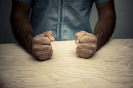 Angry businessman hit fist to table in office workstation.