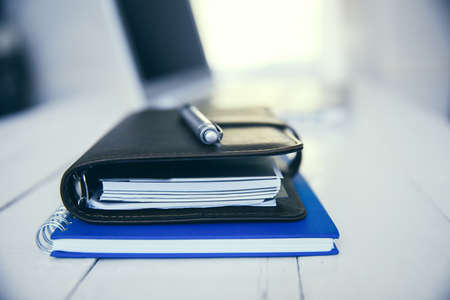 Blue notebook and black leather planner with pen on an office desk.