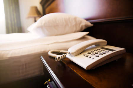 Hotel room scene with bed pillows and telephone.