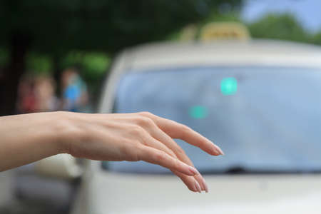 Woman catching taxi on the street. Stock Photo