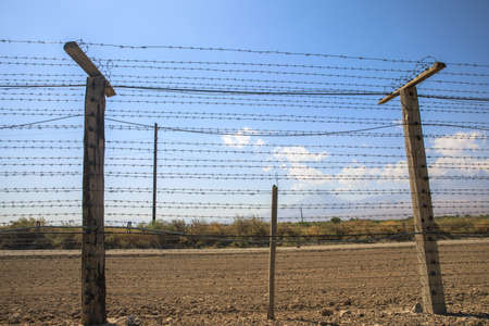 Barbed wire fence on blue sky background.